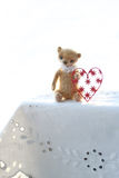 Red paper heart and the small brown toy bear made of wool sitting on a white napkin warm colors. soft focus. Royalty Free Stock Photo