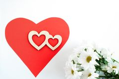 Red paper heart, two carved wooden hearts on it and white chrysanthemums on white background with copy space. Stock Image