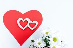 Red paper heart, two carved wooden hearts on it and white chrysanthemums on white background. Stock Photography