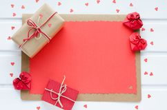 Red paper hearts with gift boxes, on white wooden background, Va. Lentine`s Day. Space to copy. Top view Royalty Free Stock Photo