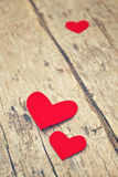 Red paper hearts on grunge wooden background Royalty Free Stock Images