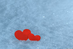 Red paper hearts in the snow. Greeting card for Valentine's Day. Royalty Free Stock Image