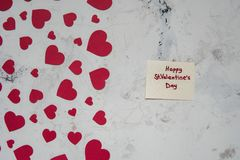 Red paper hearts on a white texture background and note with tex. T Happy St.Valentine`s Day Stock Image
