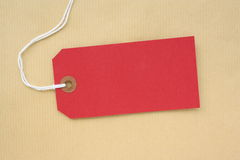 Red Paper Luggage Tag. Or label with copy space on a brown wrapping paper background Stock Image