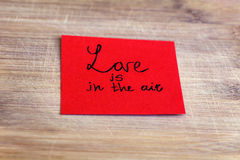 Red paper note with love is in the air sign  on a wooden background Royalty Free Stock Image