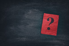 Red paper note with question marks on black board Royalty Free Stock Images