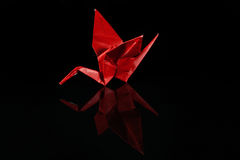 Red Paper Origami Crane On Black. An origami paper crane on black, with a slight reflection underneath and room for text on each side royalty free stock photography