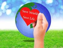 Red paper shape in hand and globe on grass background. environme Royalty Free Stock Photography