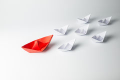 Red paper ship leading among white Royalty Free Stock Images