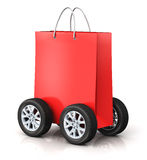 Red paper shopping bag with car wheels. Creative abstract commercial business retail sale and online shopping discount offer and free shipping and delivery Stock Photo