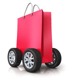 Red paper shopping bag with car wheels. Creative abstract commercial business retail sale and online shopping discount offer and free shipping and delivery Stock Images