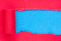 Red paper torn to reveal blue panel Royalty Free Stock Photo