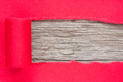 Red paper torn to reveal wooden panel Stock Image