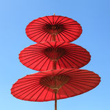 Red paper umbrella with blue sky background Stock Image