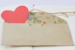 Red paper valentine in a shape of heart in vintage cardboard envelope and notebook stock photography