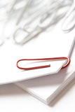 Red paperclip. On white paper selective focus Stock Photography