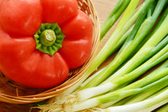 Red paprika in basket with spring onions Royalty Free Stock Images