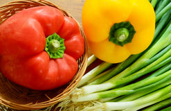 Red paprika in basket with yellow paprika and spring onions Stock Photos