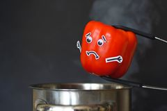 Red Paprika with sad face and goggle eyes being put into a steaming cooking pot on black background stock photos