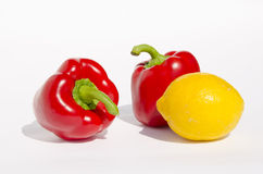 Red paprikas and yellow lemon. Royalty Free Stock Photo