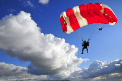 Red parachute. Landing on stormy sky Stock Image
