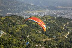 Red parachute with a blue stripe of a paraglider flying in tandem against a background of green mountains and a city in the valley. A red parachute with a blue stock photos