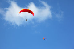 The red parachute flies in the blue sky Stock Photos