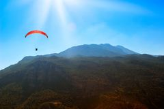 Red parachute in the sky above the mountains. Royalty Free Stock Photos