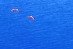 Red parachutes in the sky above the blue sea. Image in the style of minimalism. Travel concept royalty free stock photos