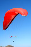 Red paraglider. Jumping from a mountain Stock Photos