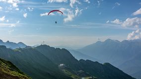 Red paraglider in blue cloudy sky over green mountains. Green valley with cable car down below. Krasnaya Polyana, Sochi royalty free stock image