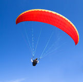 Red paraglider on the blue sky Stock Photography