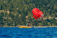 Red parasail wing pulled by a boat on lake Tahoe in California, USA. Red parasail wing pulled by a boat on lake Tahoe, summer recreation in California, USA stock photo