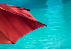 Poolside Umbrella. Red Parasol Beside Turquoise Swimming Pool Royalty Free Stock Photo
