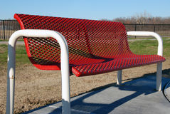 Red Park Bench. A red park bench is empty on a sunny day Royalty Free Stock Images