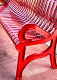 Red park bench. Painted red park bench in bright stock photo