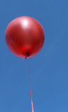 Red party balloon on blue sky Royalty Free Stock Image
