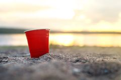Red party cup in sand at sunset. Stock Photos
