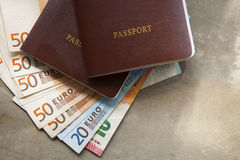 Red passport book cover and euro banknote on earth tone backgrou Royalty Free Stock Images