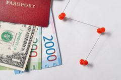 Red passport with the dollar and the new Russian banknotes rubles or euros on a white background with red pins Royalty Free Stock Photography