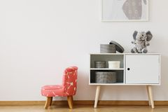 Red pattern chair next to white shelf. With boxes and plush toy in scandinavian style kids room royalty free stock images