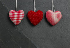 Red patterned Love Valentine's hearts hanging on grey slate ston Stock Photo