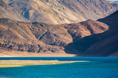 Red pavilions at Pangong Lake.Light and shade from runrise. Pangong Tso, Tibetan for long, narrow, enchanted lake, also referred to as Pangong Lake, is an Stock Photography