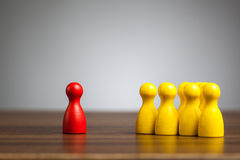 Red pawn figure against united yellow, isolation, confrontation, mobbing stock photo