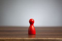 Red pawn figure toy, table, grey background. Stock Photography