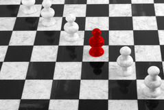 RED PAWN STANDING OUT IN A GROUP OF WHITE PAWNS Royalty Free Stock Image