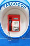 Red pay-phone on wall Stock Photography