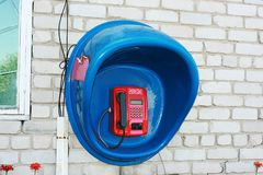 Red payphone in the blue booth. Red payphone in the blue booth on a white brick wall Royalty Free Stock Images