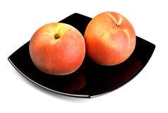 Red peaches on black dish Stock Photo