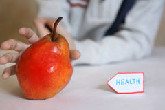 Red pear with human hand as a symbol of healthy food Stock Images